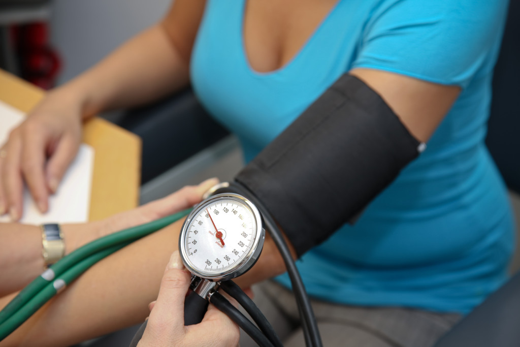 doctor with stethoscope patient attaches the blood pressure
