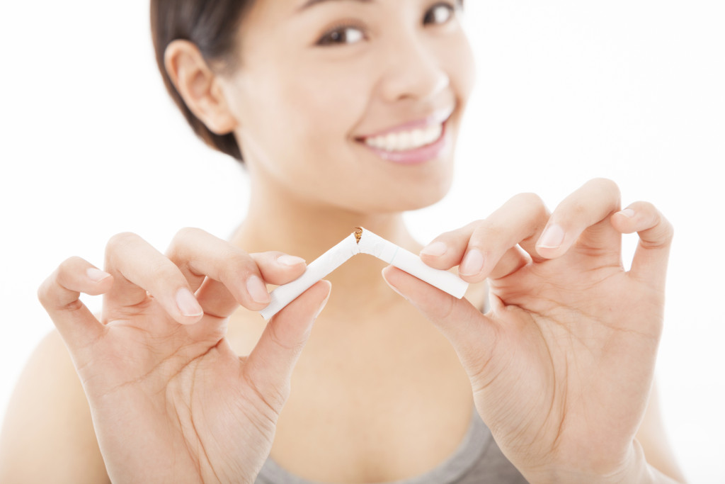 smiling woman breaking cigarette and no smoking concept
