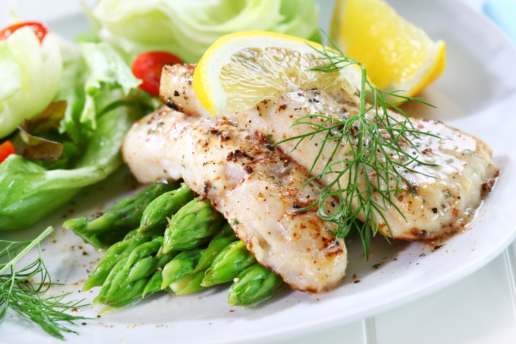 Delicious fried fish on green asparagus with salad