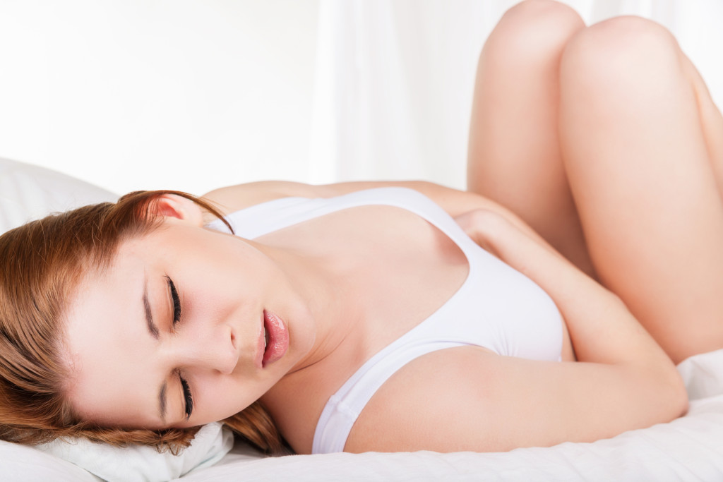 Young woman stroking her belly because of bellyache lying on bed